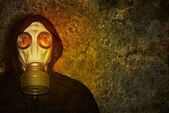 A man in a gas mask. In the light of the flame flames on a concrete wall background Stock Image