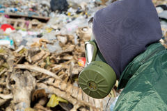 Man in a gas mask looking at garbage Royalty Free Stock Images