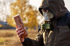 The man in the gas mask looks at the brick, a survey of dangerous infected objects careful examination. Russia Stock Image