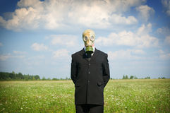 Man in gas-mask on meadow. Stock Photo