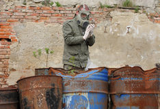 Man with gas mask and  military  clothes  explores  dead bird. Stock Photography