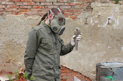 Man with gas mask and  military clothes  explores   dead bird Stock Image
