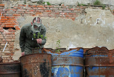 Man with gas mask and  military clothes  explores  small plant Royalty Free Stock Images