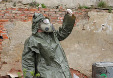Man with gas mask and  military clothes  explores  small plant Royalty Free Stock Photography