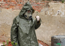 Man with gas mask and  military clothes  explores  small plant Stock Photos