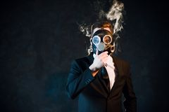 Man gas mask nicotine cloud passive smoker danger. Man covering his face with a gas mask surrounded by nicotine smoke. Danger of being passive smoker concept royalty free stock photo