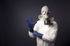 Man with a gas mask puting on his gloves Stock Image