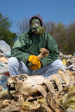 Man in a gas mask sitting on the garbage and holding a bone Stock Image