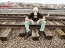 Man in gas mask sitting on the rails. Resting Royalty Free Stock Photo