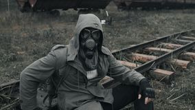 Man in gas mask sitting on railway by rusty carriages at deserted train station