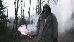 Man in gas mask standing in empty dead forest, holds red signal fire in hand