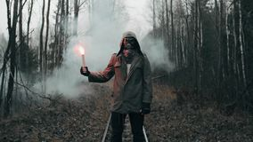 Man in gas mask standing on railway in dead forest holding signal fire in hand