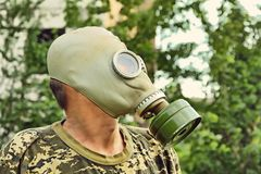 Man in gas mask taken closeup on overgrown urban background. Apocalyptic concept royalty free stock photography