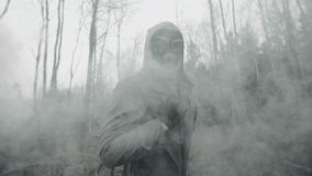 Man in gas mask walking on old railway in clouds of toxic smoke post apocalypse
