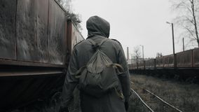 Man in gas mask walks near abandoned rusty carriages at destroyed train station