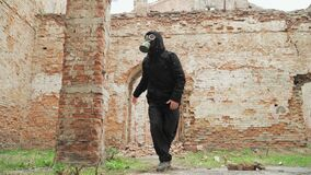 A man in a gas mask walks through the ruins. Doomsday concept. After the war
