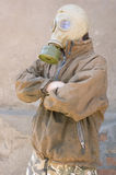 Man in gasmask. Man in gas mask and dirty uniform against concrete wall Stock Image
