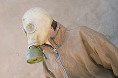 Man in gasmask. Man in gas mask and dirty uniform against concrete wall Royalty Free Stock Images