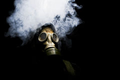 Man in gasmask. With abstract smoke on black background Stock Image
