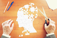 Man gathers a human head as puzzles on the desk. Man gathers a human head as puzzles on the wooden desk Stock Photography