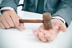Man with a gavel in his hand. Closeup of a young caucasian man in suit sitting in a desk with a wooden gavel in his hand Royalty Free Stock Photography