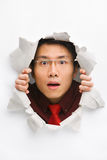 Man gazing surprisingly from hole in wall. With copy space in horizontal position royalty free stock photography