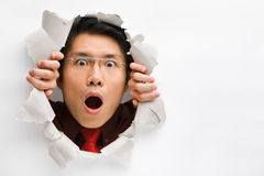 Man gazing surprisingly from hole in wall. With copy space in horizontal position royalty free stock image