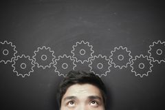 Man with gears on the blackboard Stock Images