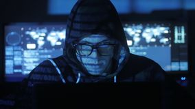 Man geek hacker in hood with glasses working at computer while blue code characters reflect on his face in cyber