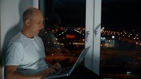Man genom att använda anteckningsboksammanträde på fönsterbräda med panoramautsikt på nattcityscape lager videofilmer