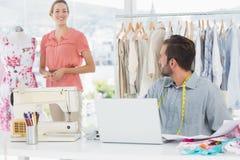 Man genom att använda bärbara datorn med modeformgivaren som arbetar på studion royaltyfri fotografi