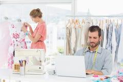 Man genom att använda bärbara datorn med modeformgivaren som arbetar på studion arkivfoto