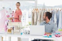 Man genom att använda bärbara datorn med modeformgivaren som arbetar på studion royaltyfria bilder