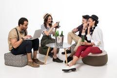 Man genom att använda bärbara datorn medan lyckliga unga vänner som dricker öl Fotografering för Bildbyråer