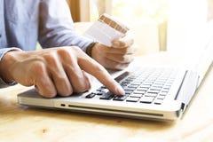 Man genom att använda bärbara datorn och mobiltelefonen till online-shopping och betala vid kreditkorten Royaltyfri Foto