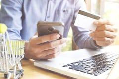 Man genom att använda bärbara datorn och mobiltelefonen till online-shopping och betala vid kreditkorten Arkivfoton