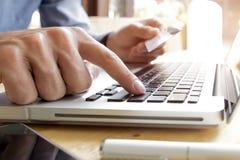 Man genom att använda bärbara datorn och mobiltelefonen till online-shopping och betala vid kreditkorten Royaltyfri Bild
