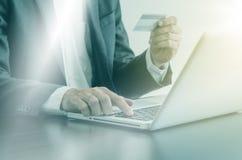 Man genom att använda datoren med en kreditkort till att shoppa direktanslutet Arkivfoto