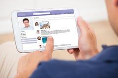 Man genom att använda den digitala minnestavlan för att prata på social plats Arkivbild