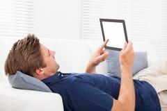 Man genom att använda den digitala minnestavlan med den tomma skärmen på soffan Arkivfoton