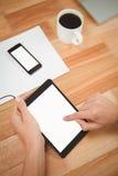 Man genom att använda den digitala minnestavlan med smartphonen och kaffe på tabellen Royaltyfri Bild