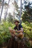 Man genom att använda den digitala minnestavlan, medan vila på trädstubben royaltyfria bilder