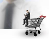 Man genom att använda den digitala minnestavlan och sitta på shoppingvagnen Arkivbilder