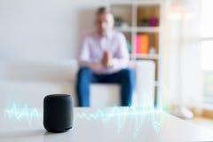 Man genom att använda den faktiska assistenten, smart högtalare hemma royaltyfria foton