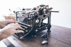 Man genom att använda den manuella skrivmaskinen för tappning på den lantliga trätabellen med retur för vagn för rörelsesuddighet arkivfoton