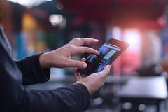 Man genom att använda den mobila smartphonen för online-bankrörelsen i kafeteria arkivfoton