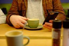 Man genom att använda den nära smartphonen upp i kafét fotografering för bildbyråer