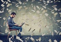 Man genom att använda en bärbar dator som bygger online-pengar för affärsförtjänsten under kassa för dollarräkningar som ner fall royaltyfria foton