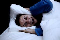 Man genom att använda en kudde för att täcka hans öron royaltyfri fotografi