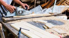 Man genom att använda en malande maskin på trä, det Wood hantverket Royaltyfri Bild